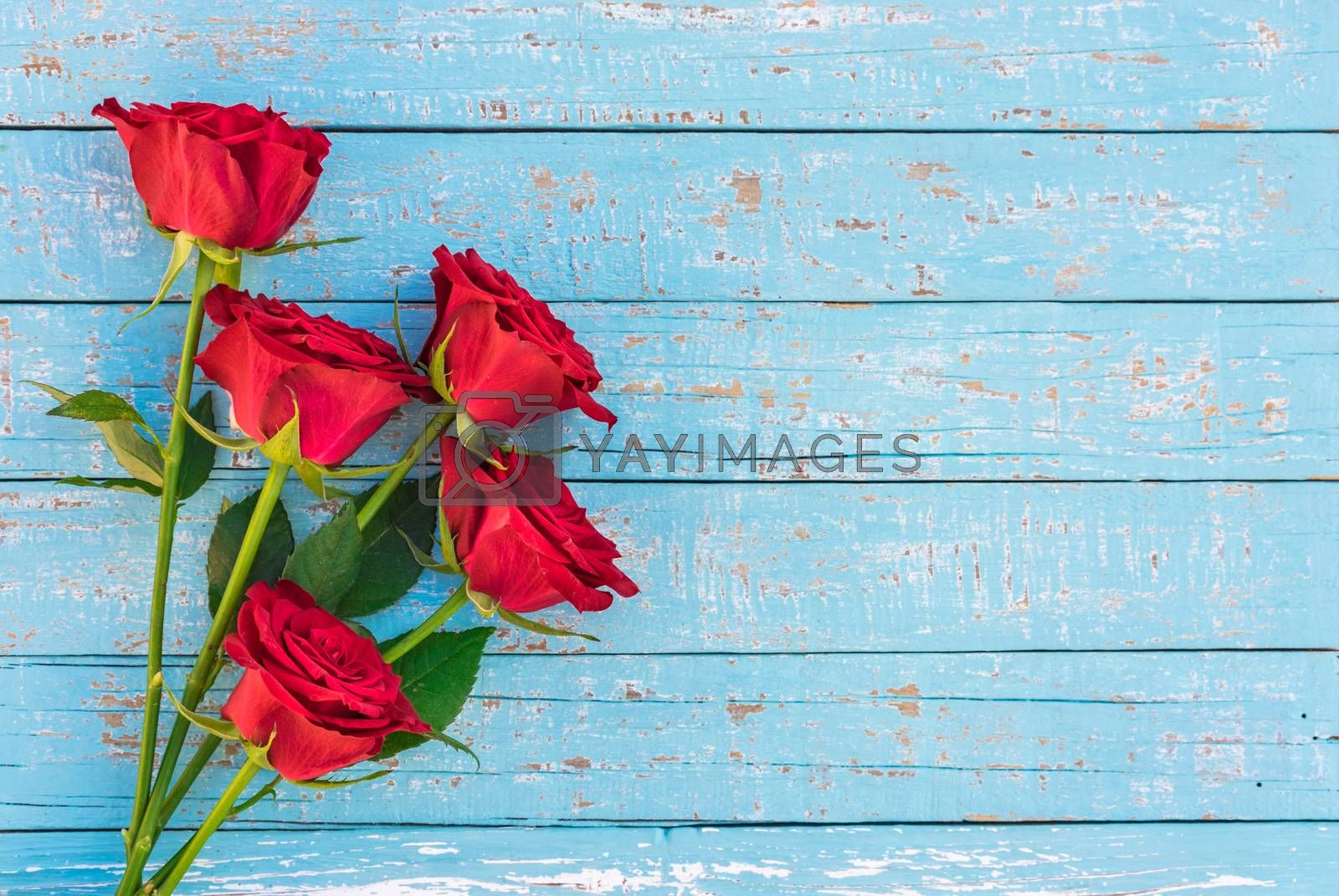 Romantic bunch of red rose flowers on blue wooden background with copy space