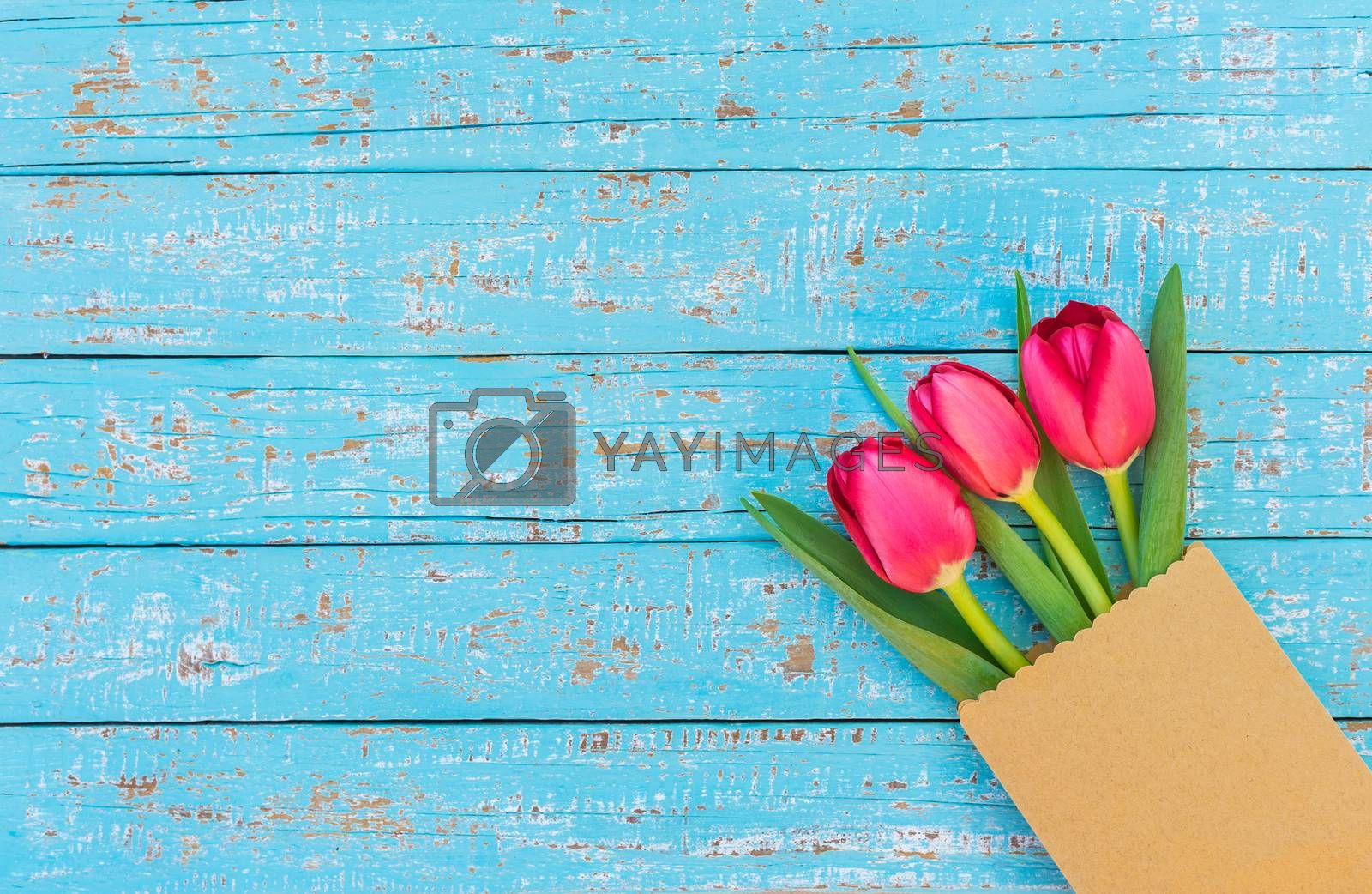 Red tulip spring flowers in paper bag on turquoise wood with copy space