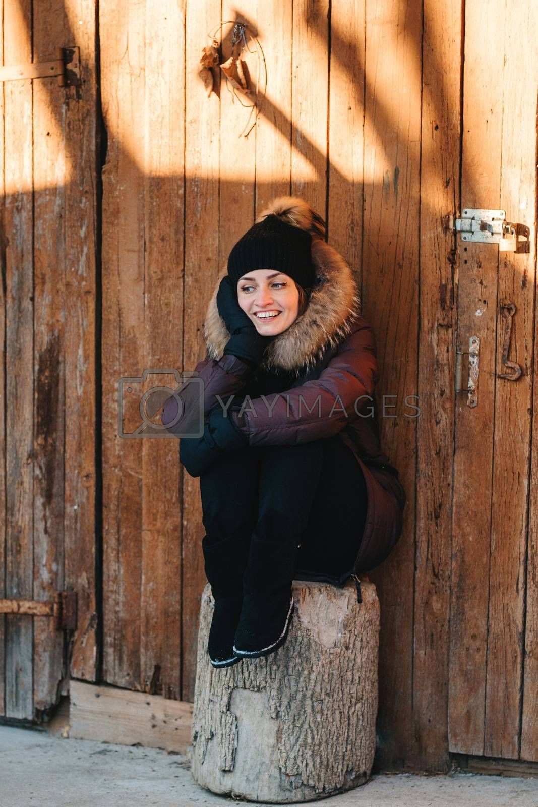girl looks at a guy who cuts firewood in the yard, covered with snow