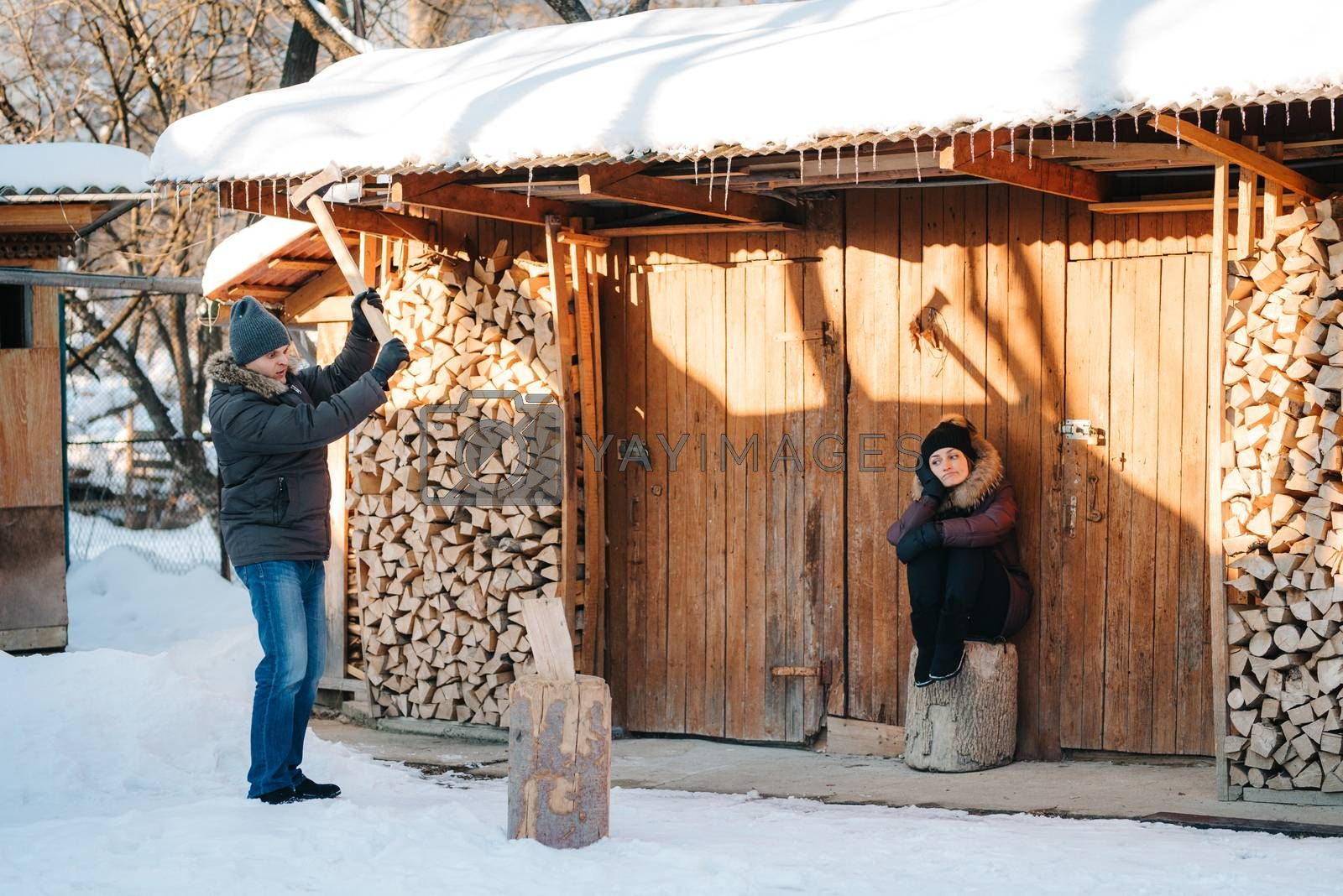 guy in winter clothes chopping wood in the yard, covered with snow