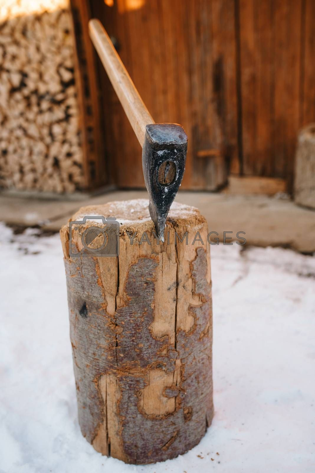 an ax sticking out in a wooden deck in a snowy village courtyard