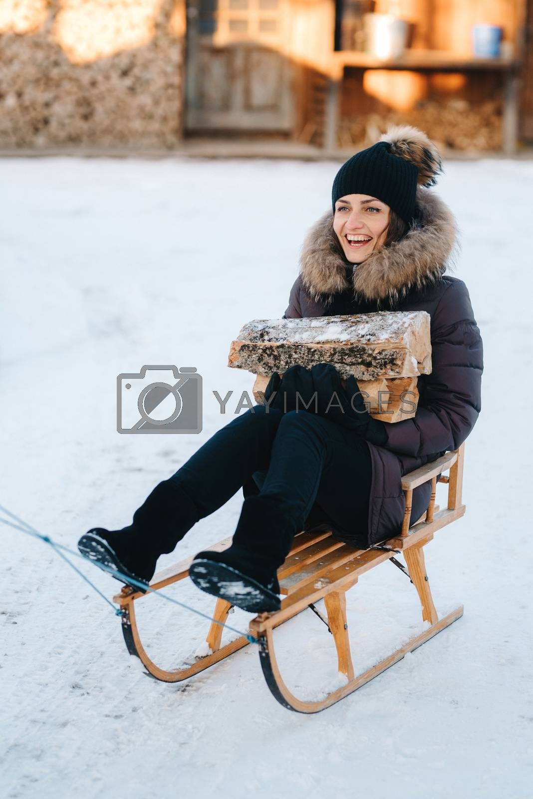 girl sitting in a sled, smiling and holding a wooden log in her hands
