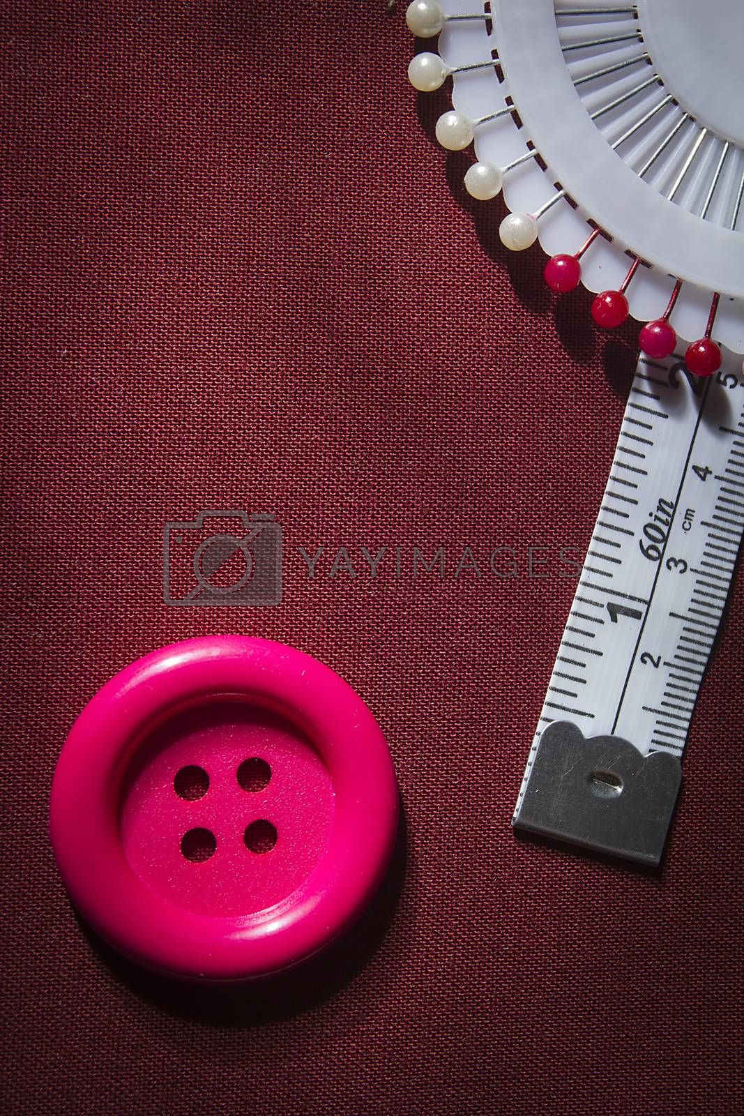 Button and tailor meter on fabric background