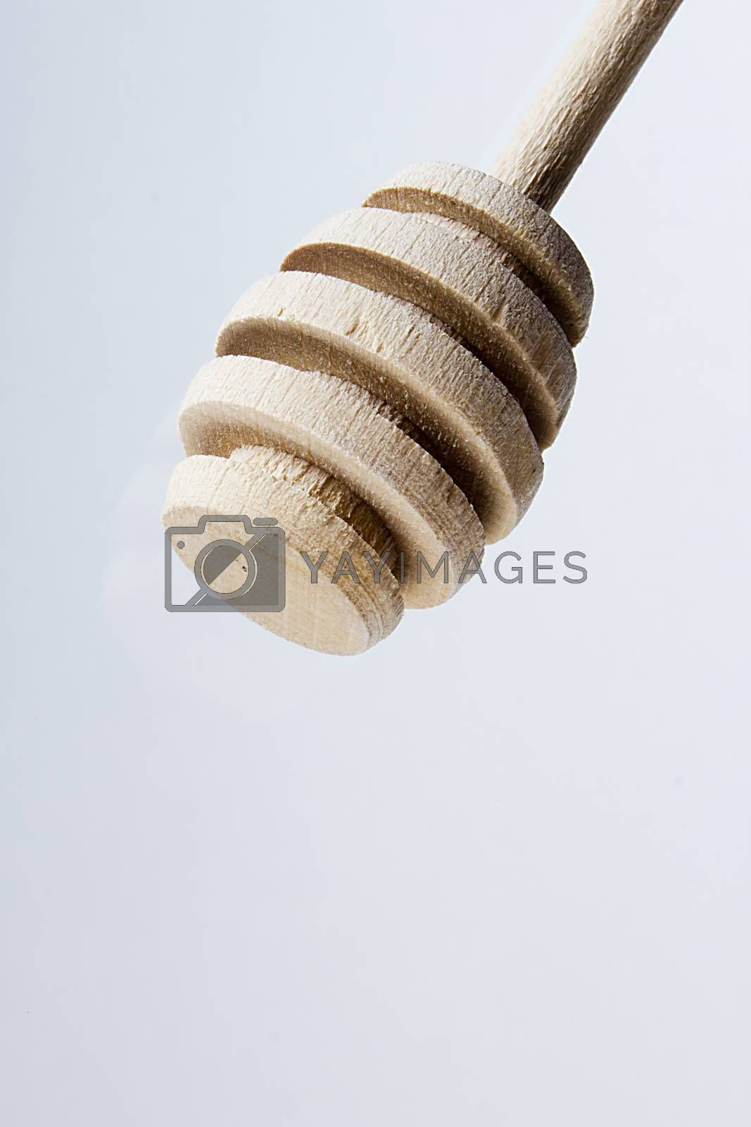 Traditional wooden honey dipper on a gray background