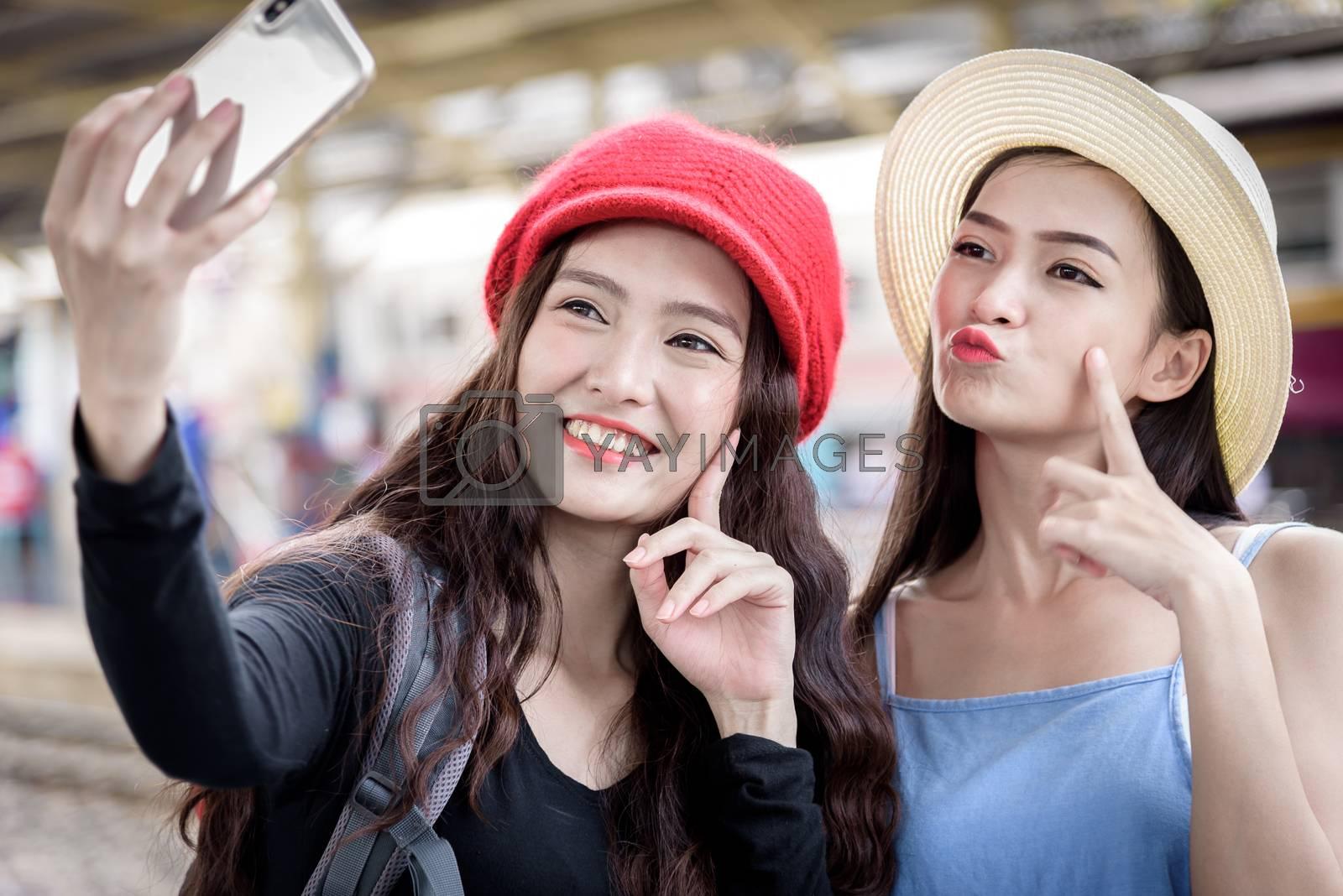 Asian women traveler have playing a mobile phone and talking for waiting the train with happiness at Hua Lamphong station at Bangkok, Thailand.