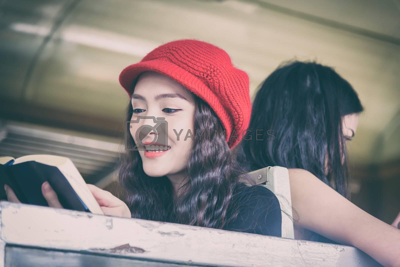 Asian women traveler have reading a book and talking in the train with happiness at Hua Lamphong station at Bangkok, Thailand.
