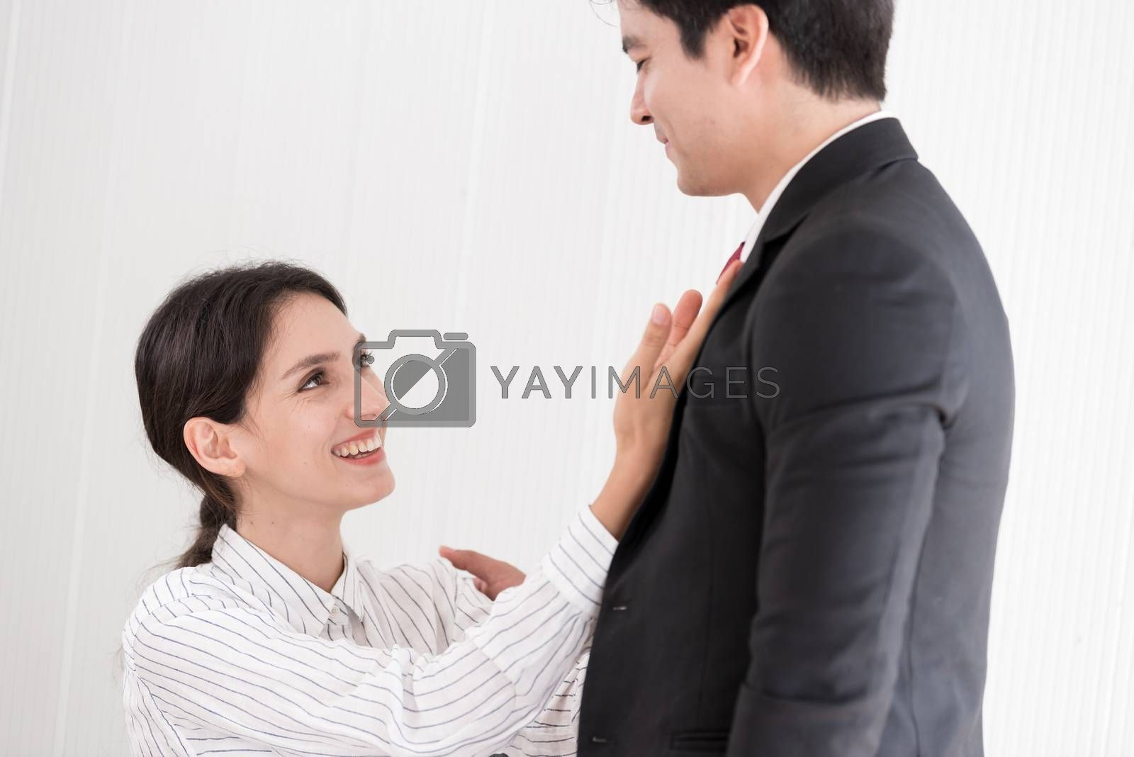 Wife tying red necktie to her husband in the office with smiling by animagesdesign