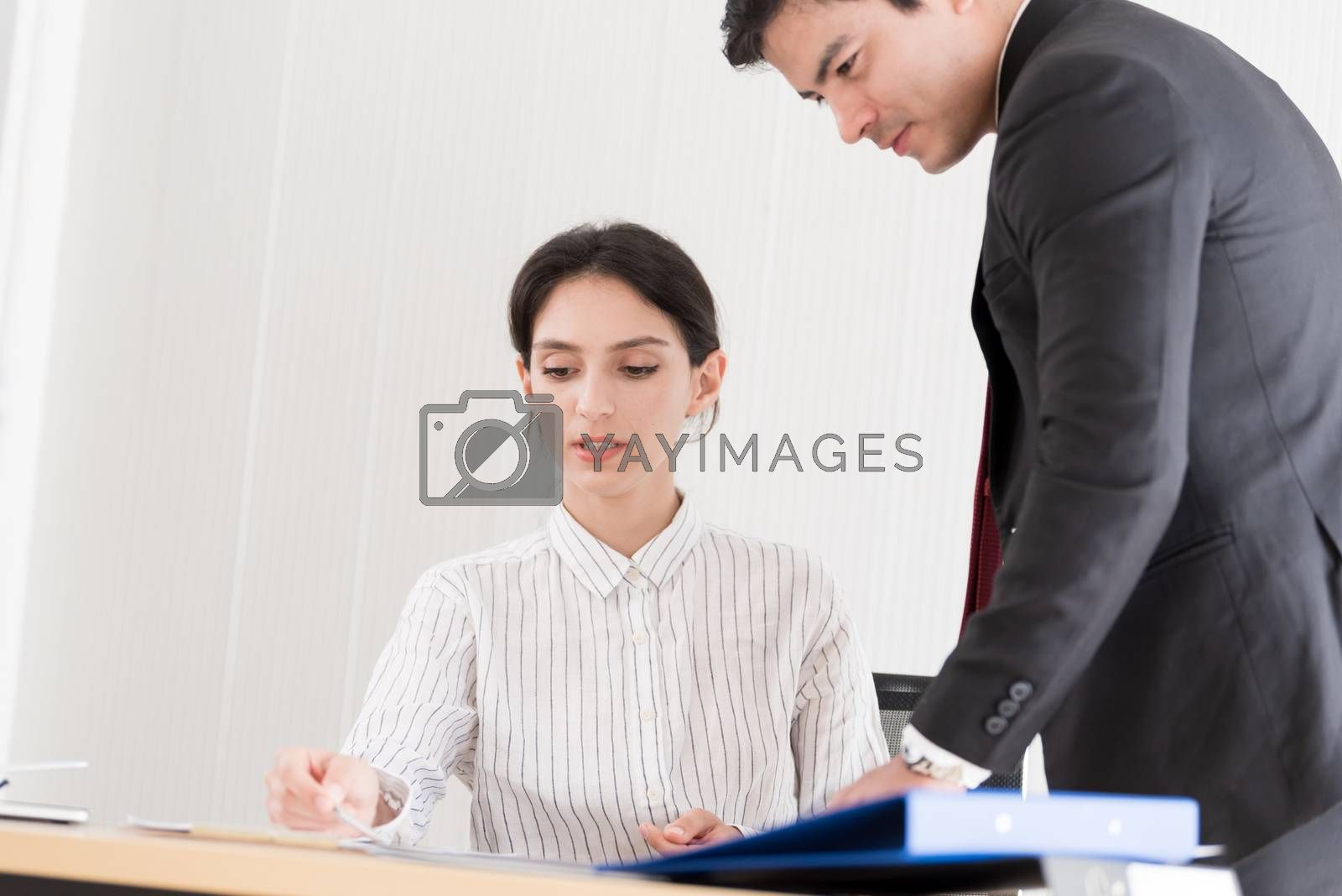 A manager and secretary working together in the office. by animagesdesign
