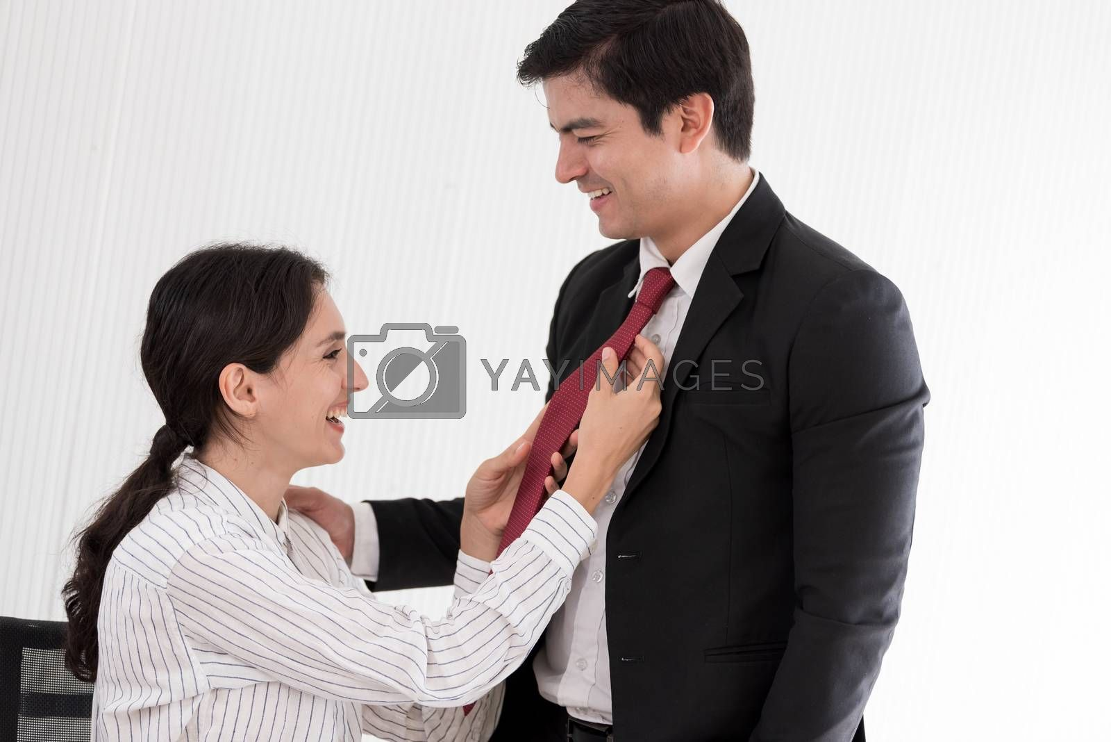 Wife tying red necktie to her husband in the office with smiling and happy.