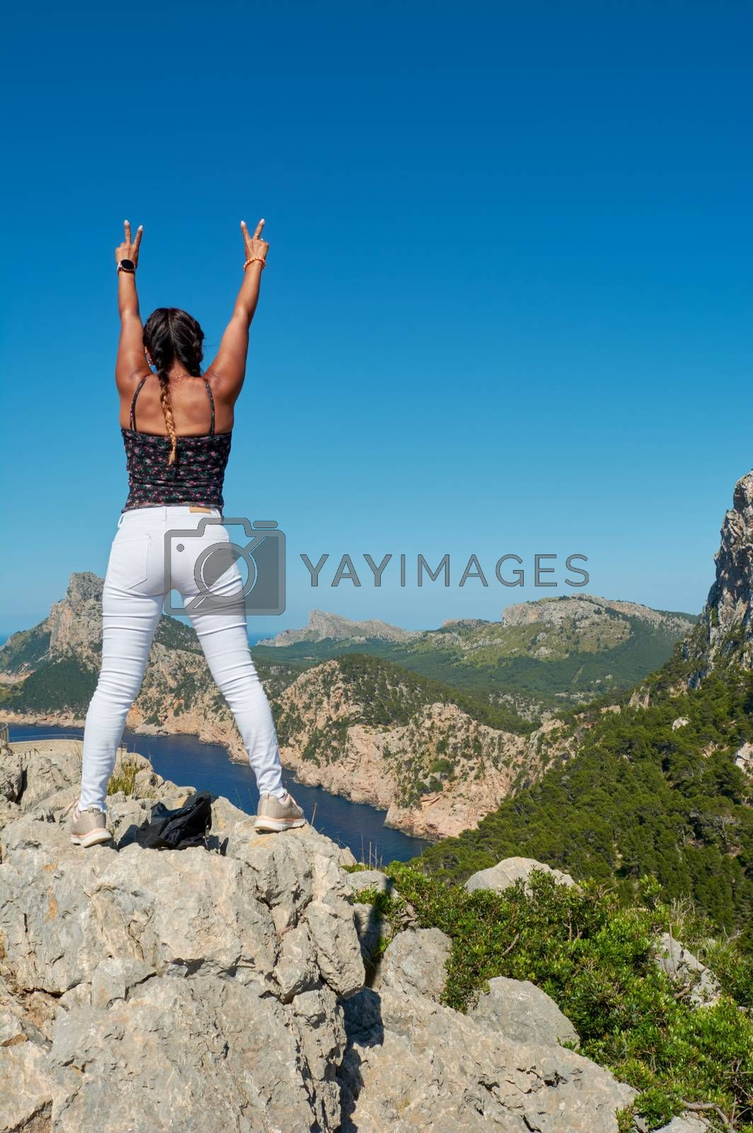 Portrait of a beautiful young hispanic latina woman, doing v sign, on the mountain cliff, cabo formentor, majorca,