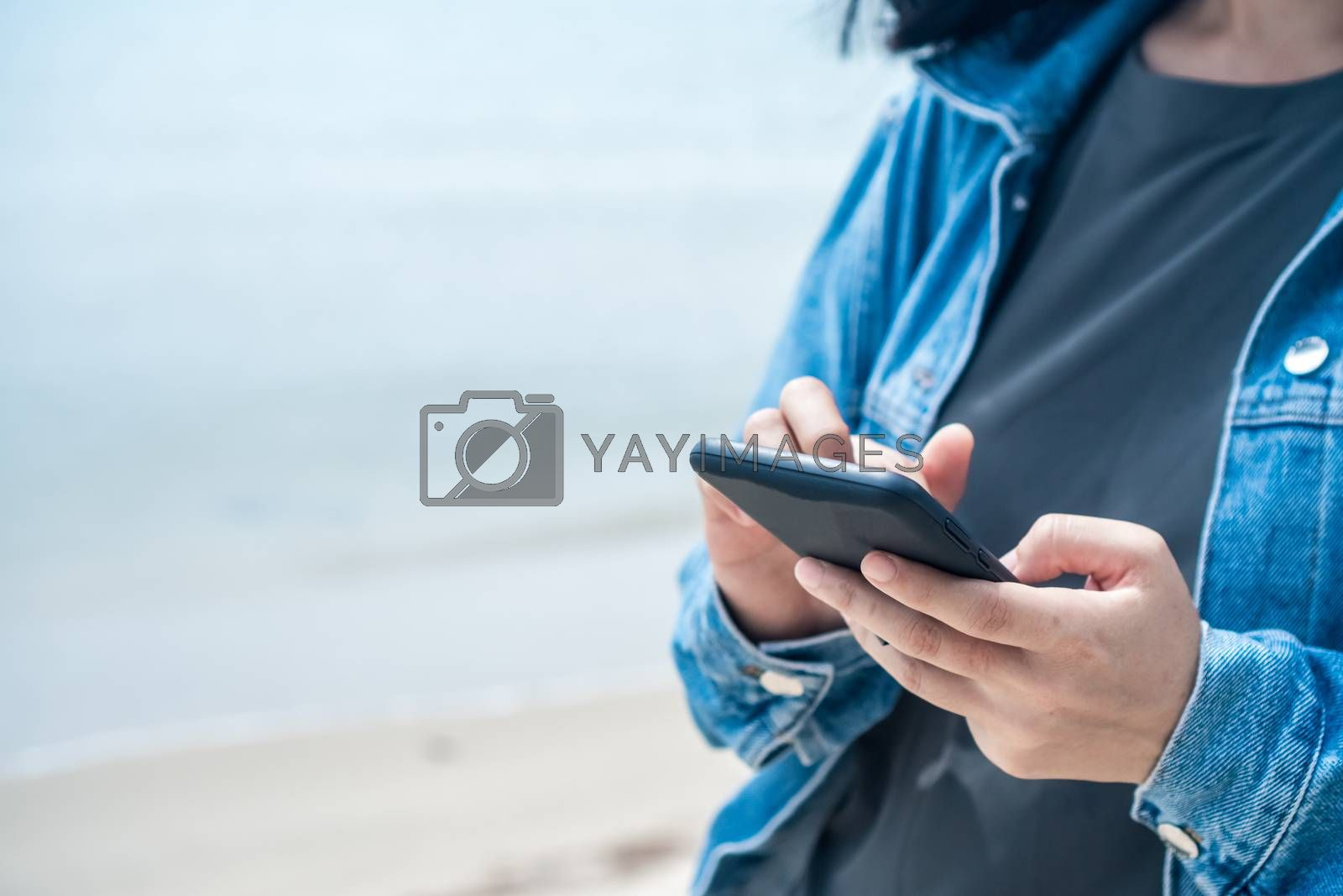 Woman using smartphone to do work business, social network, communication with beach outdoor background.