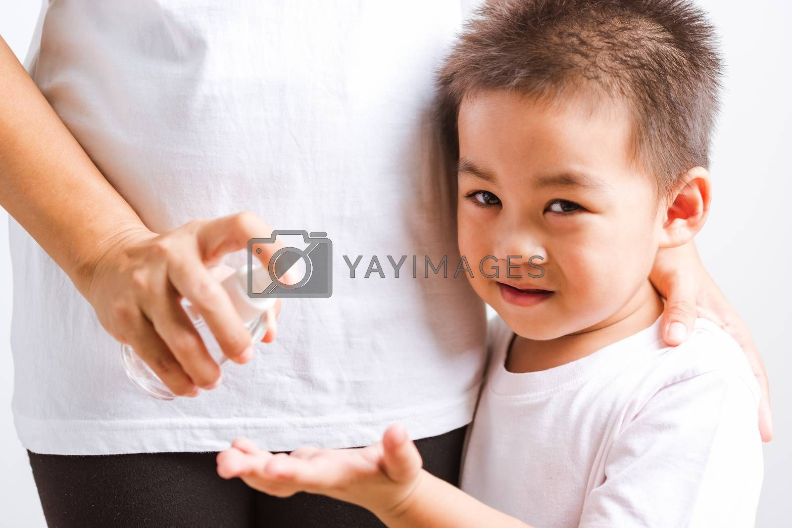 Closeup Asian Mother applying bottle pump dispenser sanitizer alcohol gel cleaning washing hands little child boy COVID-19 or coronavirus protection concept, isolated white background with copy space