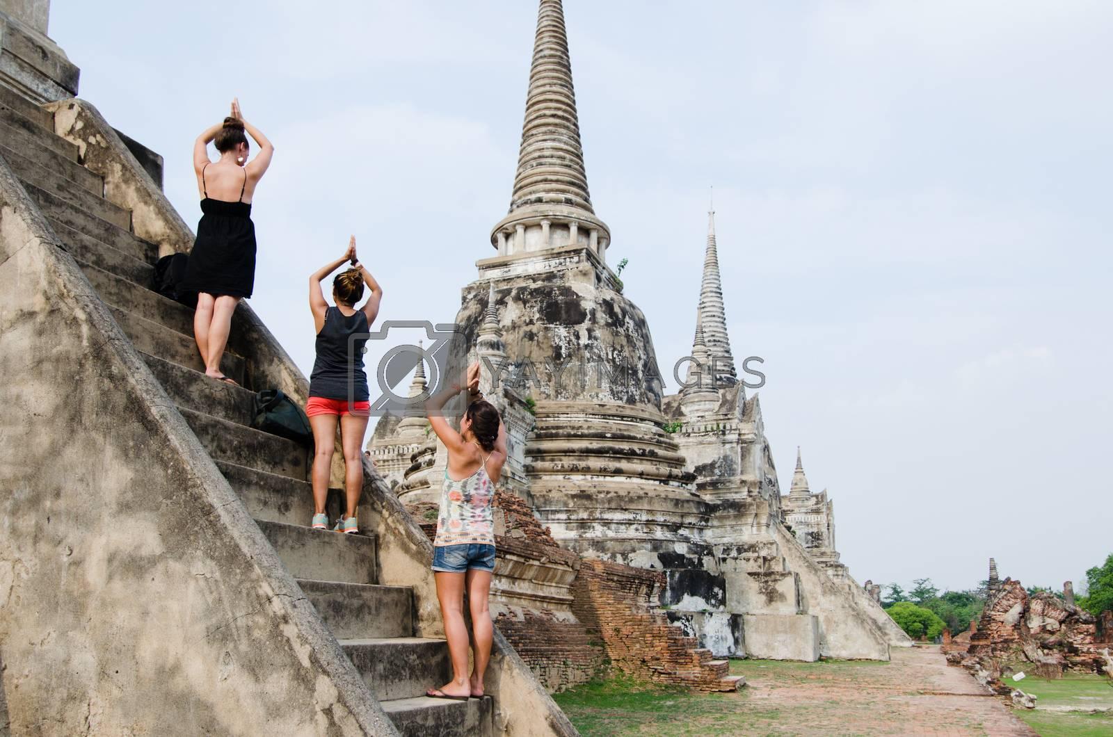 Ayutthaya, Thailand - 29 Apr 2014: Three female tourists mimic a yoga pose, aligned on the stone steps of Wat Pra Si Sanphet Buddhist shrine stupas in Ayutthaya, Thailand