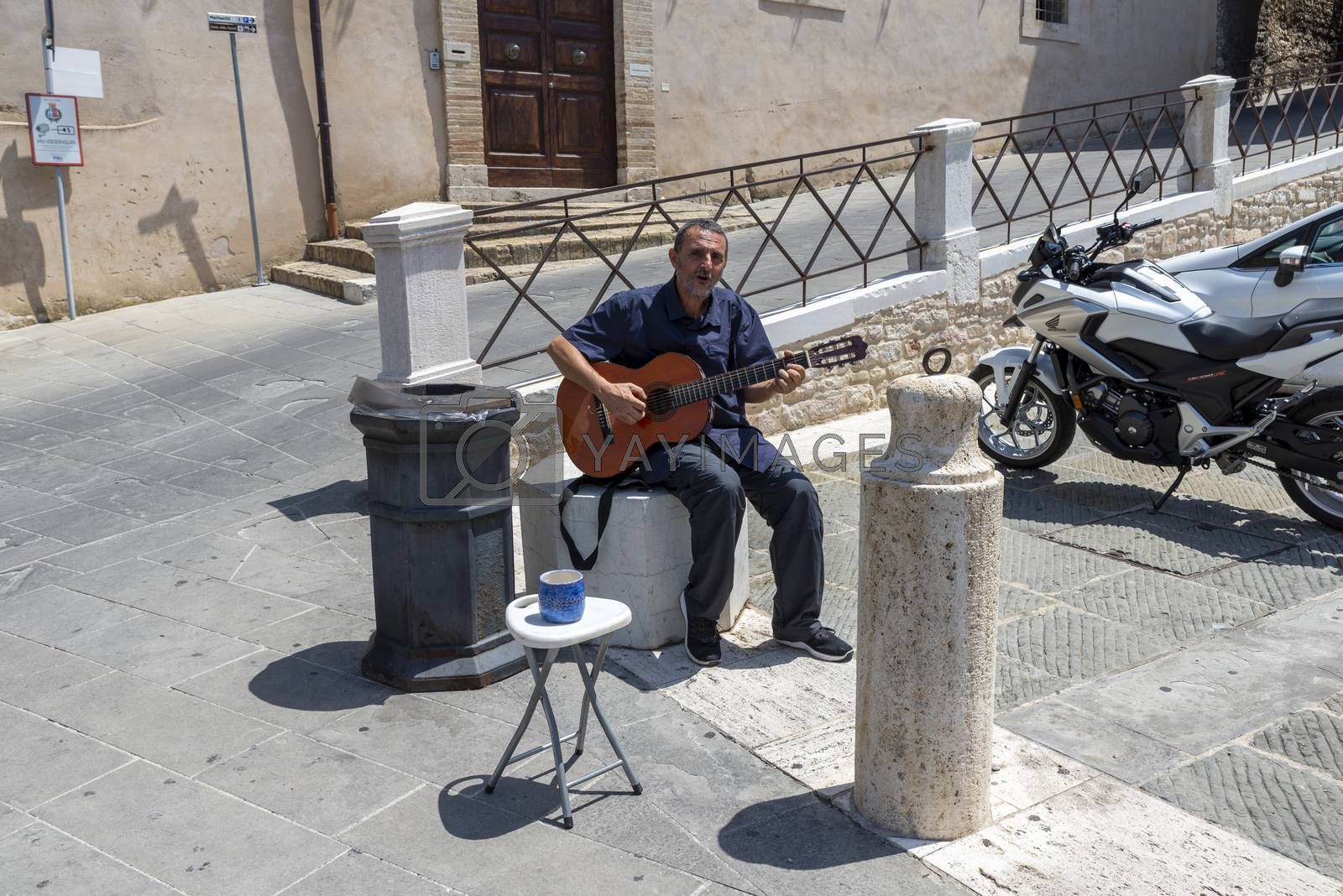 assisi,italy july 11 2020:a street artist with a guitar in the sun