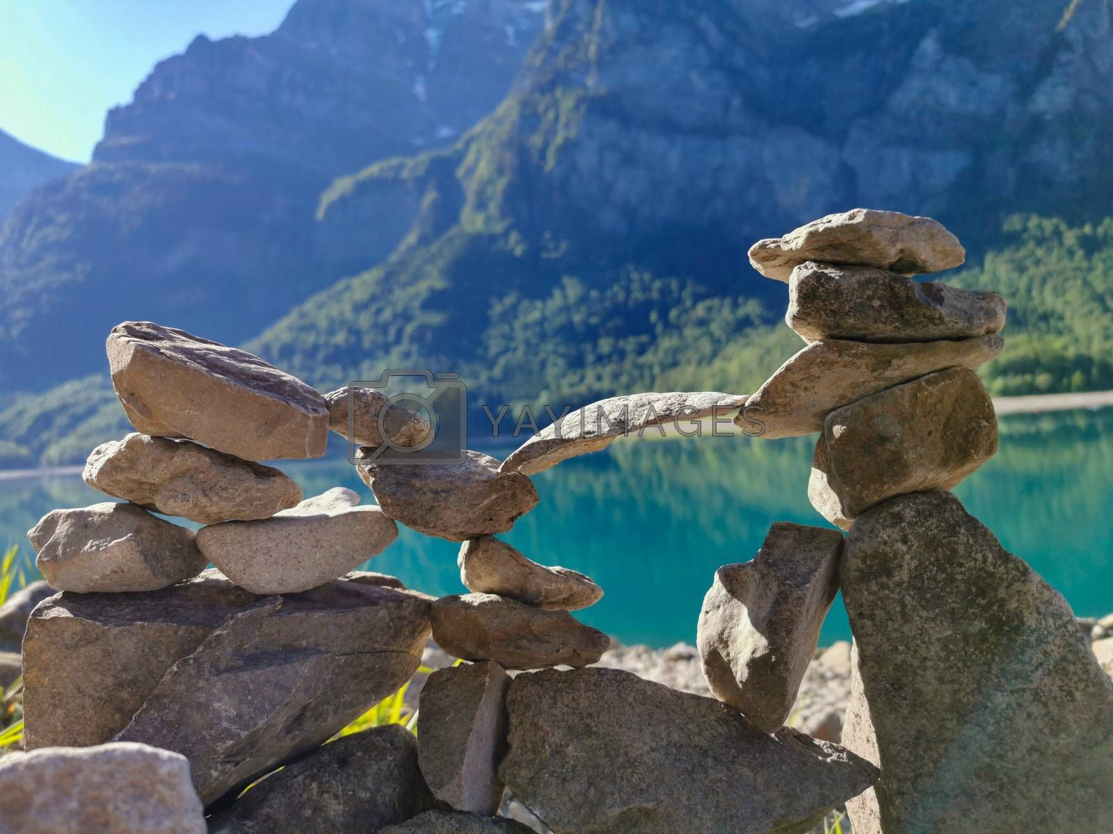 Stones stacked on top of each other with lake and mountain background