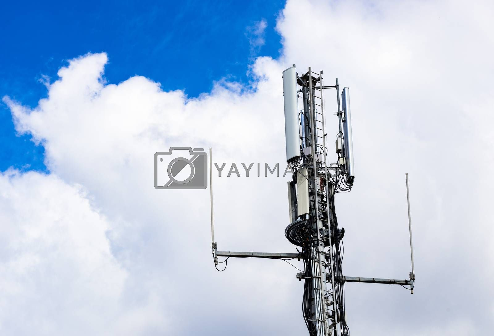 Detail view of telecommunication tower with cloudy sky background