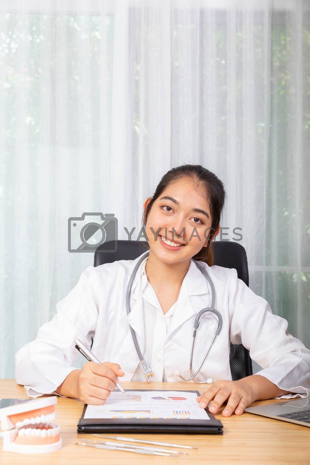 A women doctor is smiling working with her computer notbooke in her office in hospital