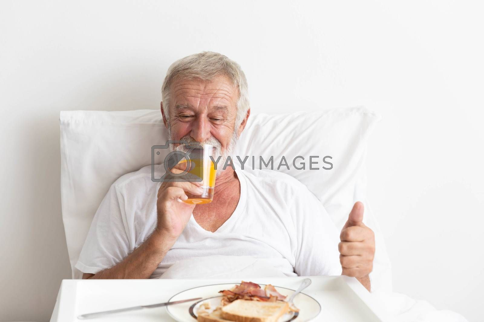Senior retirement male happy having breakfast with orange juice and water on bed
