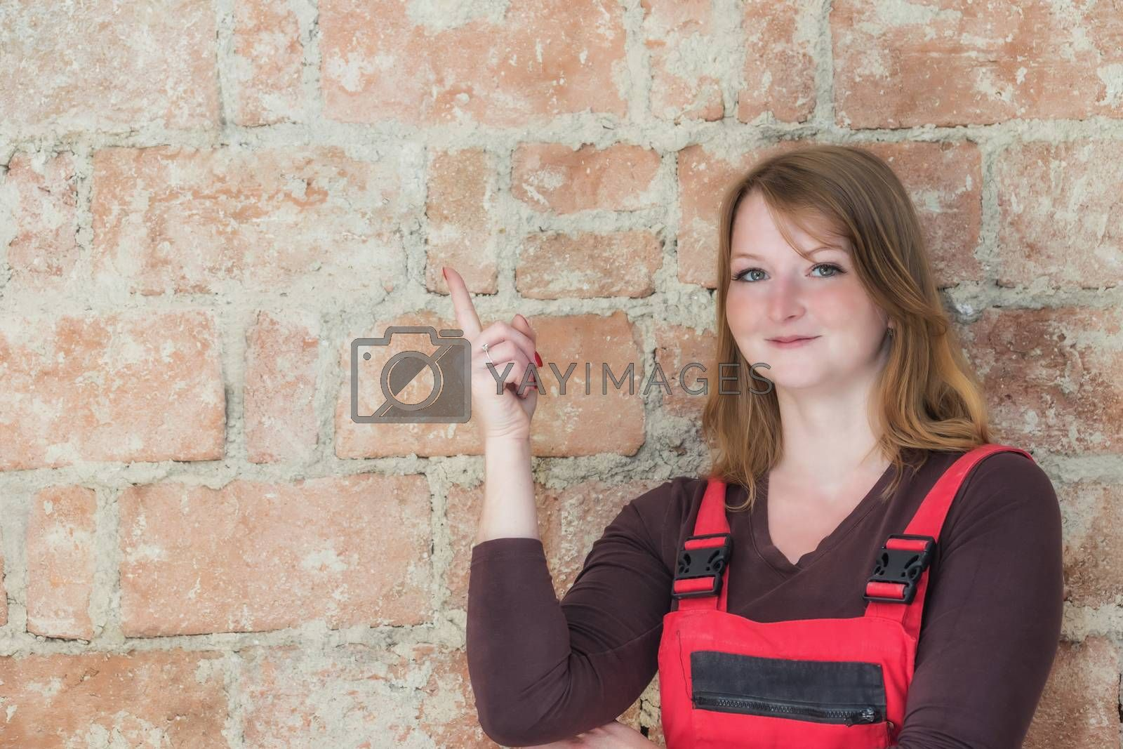Attractive young redhead woman dressed in red overall is standing  in front of an old brick wall. Woman is looking at the camera and is pointing the finger at the wall.  Place for your text is in the left half of the image.