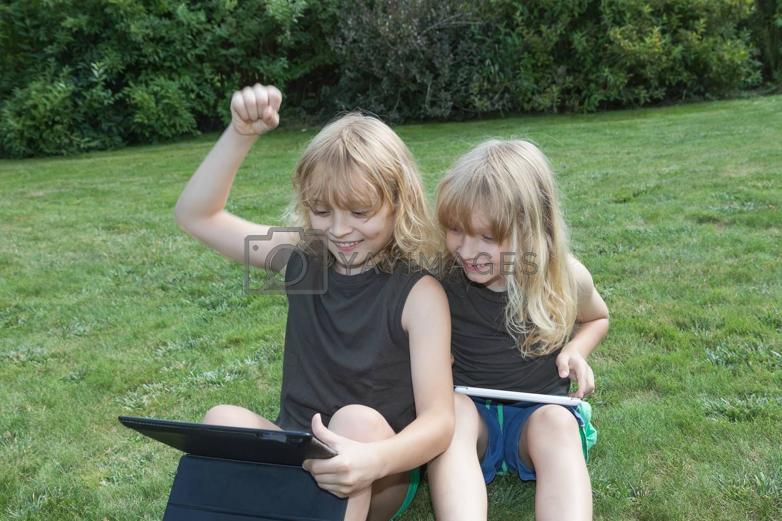 Two blond brothers are sitting on the lawn and playing games on the tablets. Boy sitting on the left is winner. He has raised his left hand.