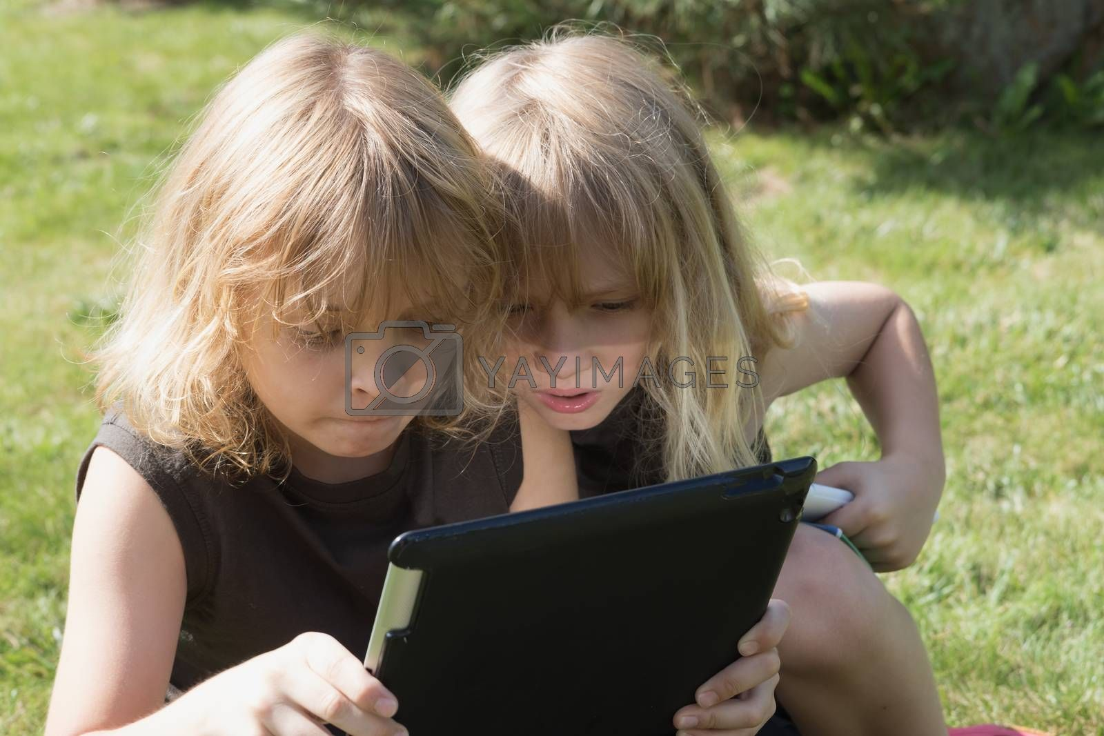 Two blond brothers are sitting on the grass and looking to the tablet. Boy sitting on the right has an open mouth and is impressed  by what he  see on the tablet. All potentials trademarks are removed,
