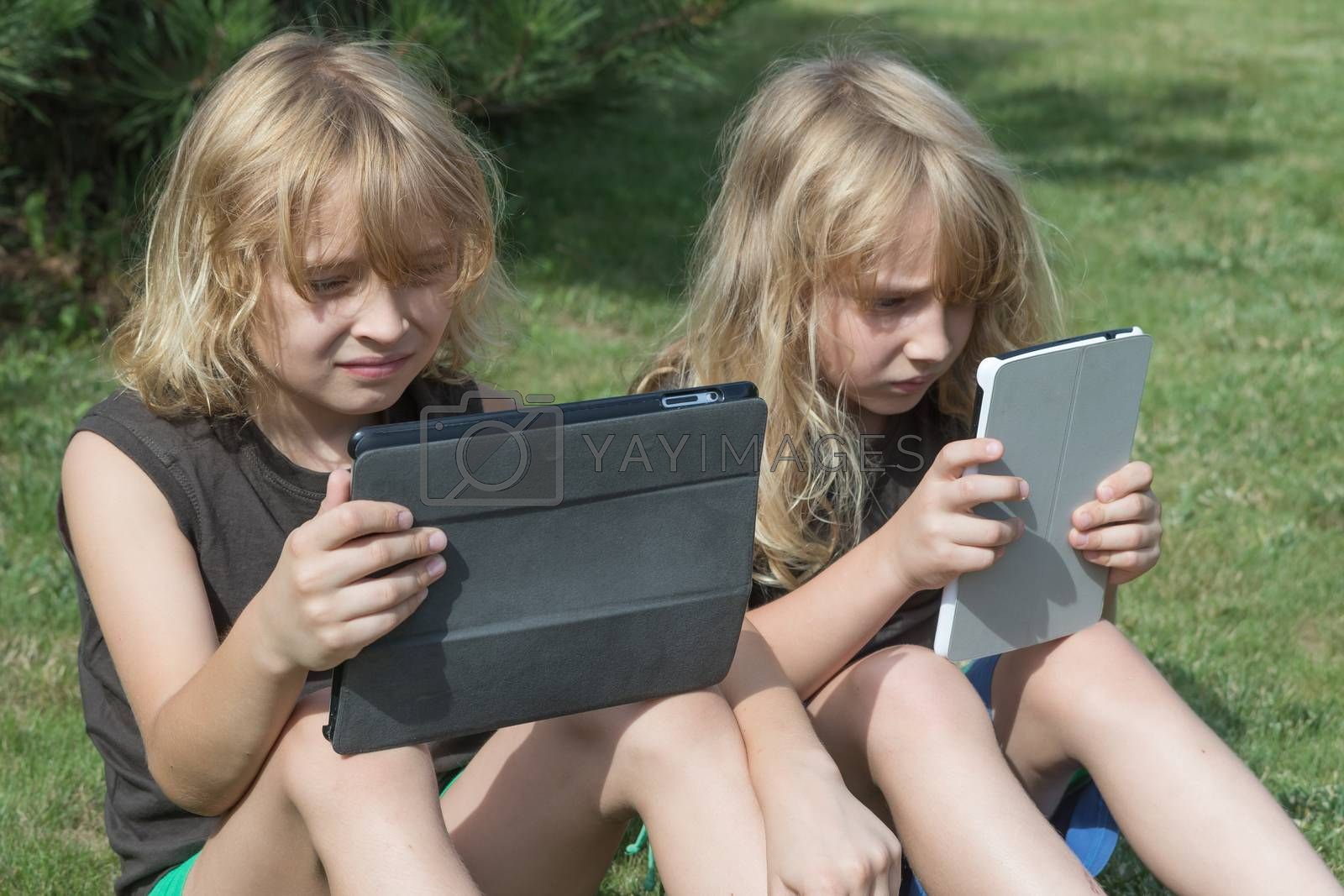 Two blond long haired boys are sitting on the lawn and are looking to the tablet. Both boys have opened their tablets. All potential trademarks are removed.