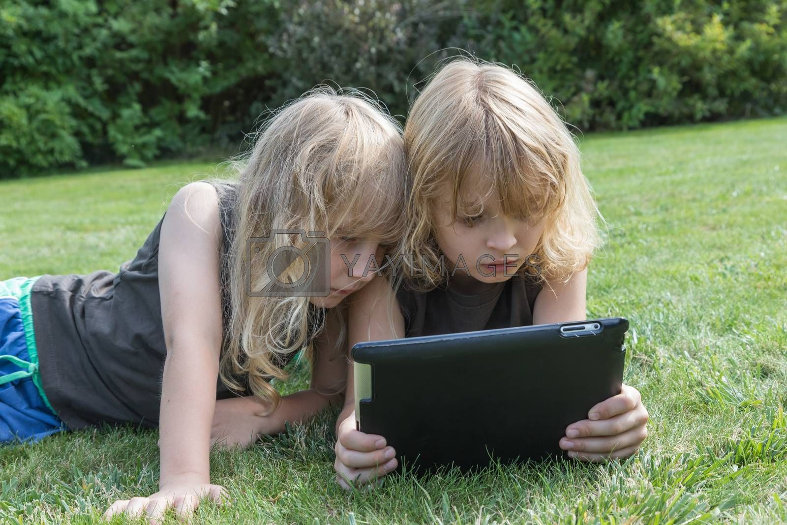 Two long haired blond boys are lying on the lawn and looking to the tablet.