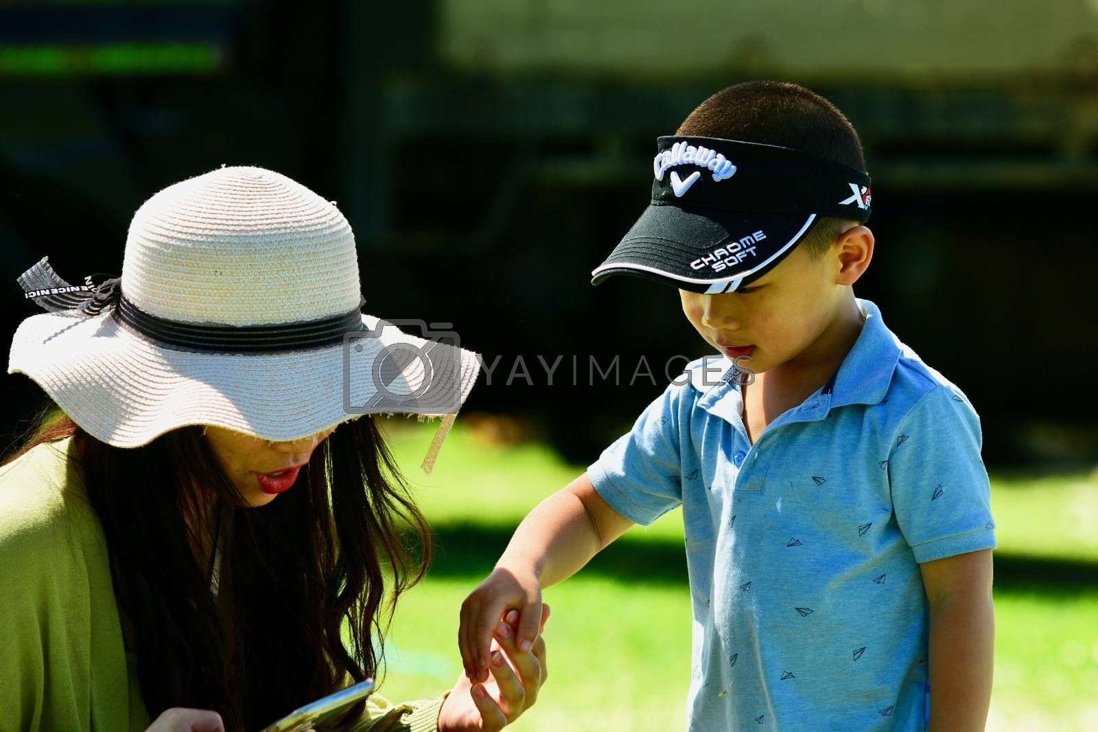 An unidentified young asian woman talking to her little son