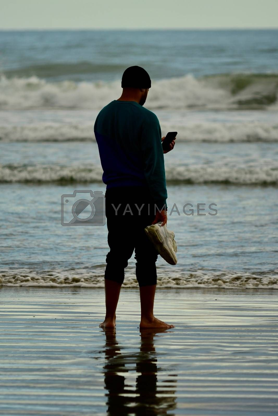 Leisure activities; walking on a beach; a man reading on his phone; taking a photo with a phone camera