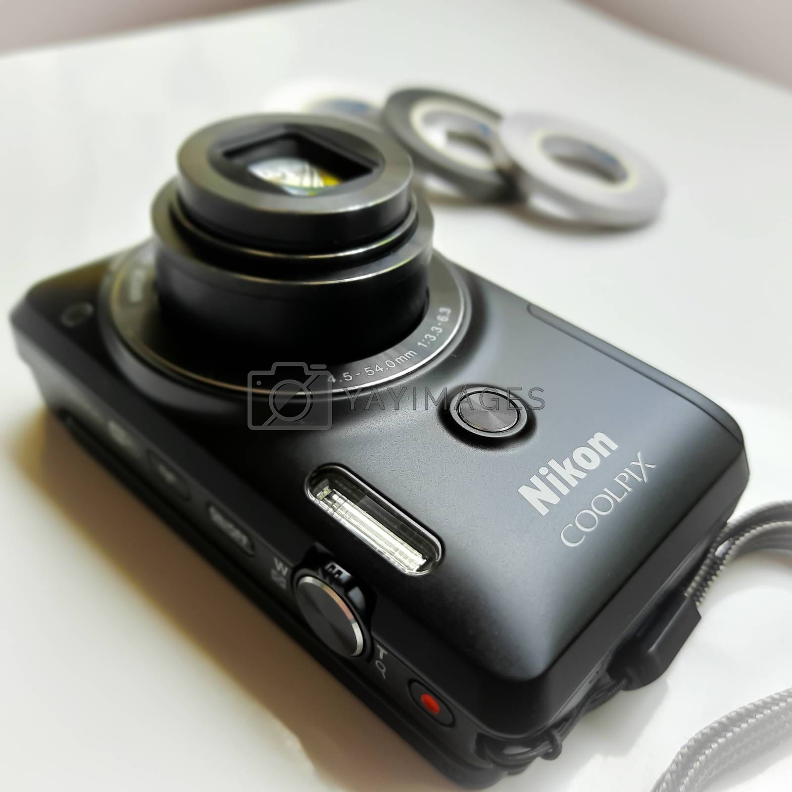 Chennai, India - July 3 2020: Digital Camera or point-point camera placed in white background with small round ribbons for decoration
