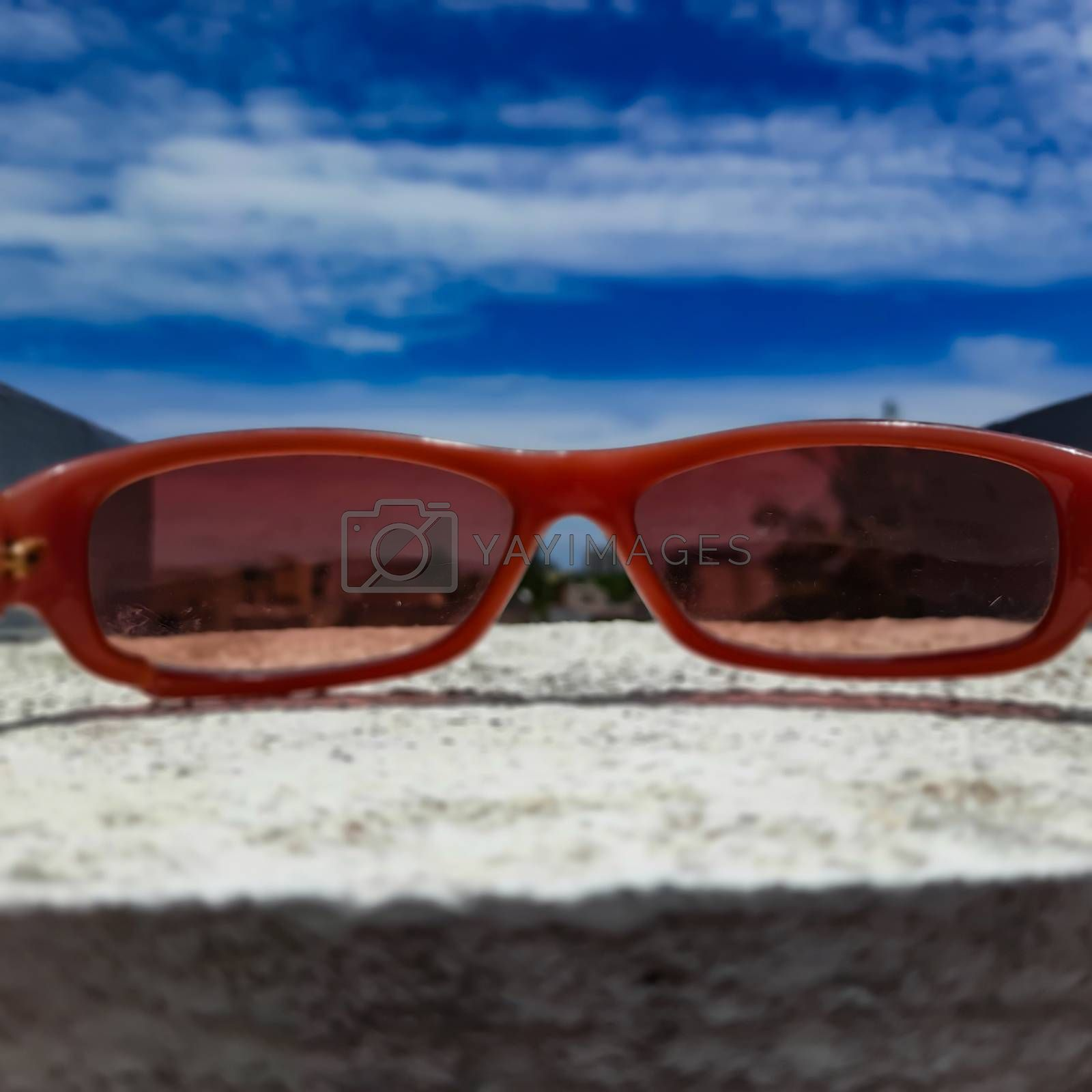 Chennai, India - July 3 2020: Red color glass placed in wall to see beautiful view of the sky from the glass lens