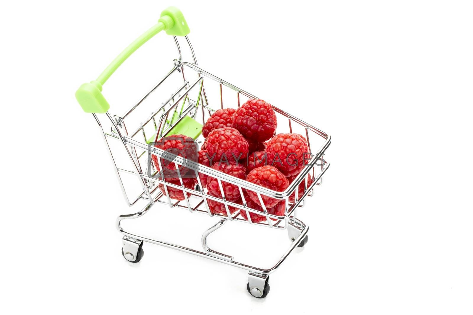 Fresh raspberries in miniature shopping cart. Isolated on white background.