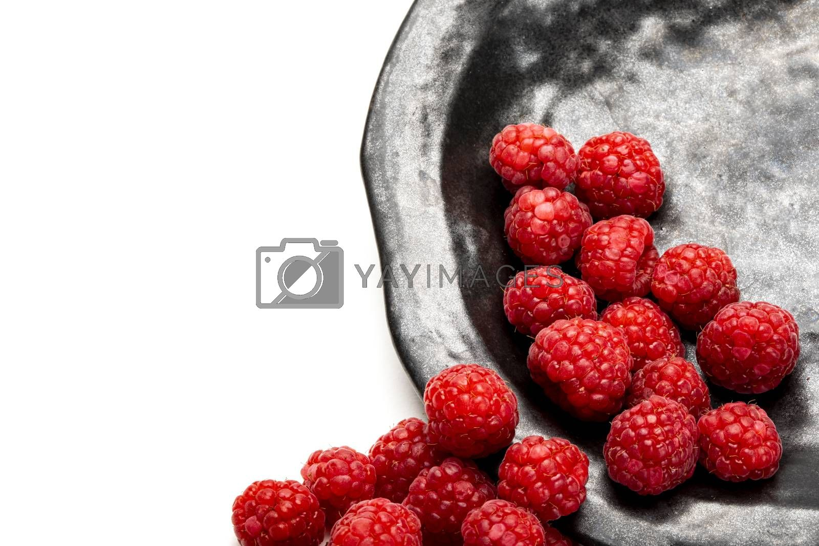 Fresh raspberries on a charcoal black plate. Isolated on white background.