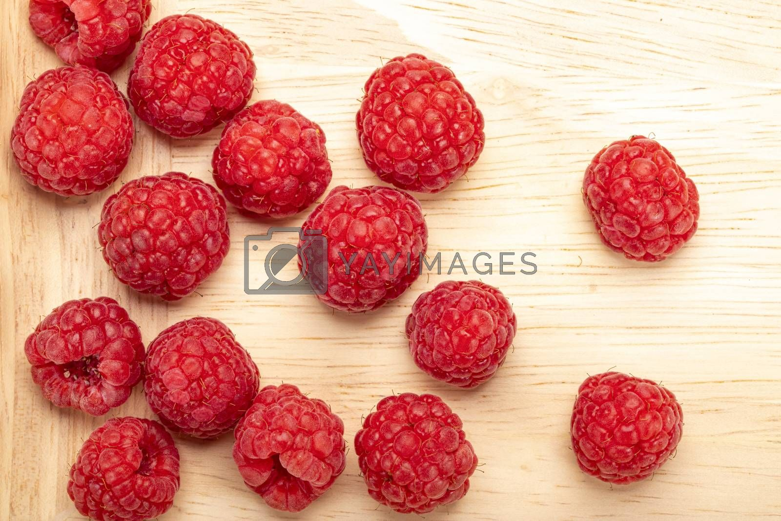 Fresh ripe raspberries on a wooden plate.