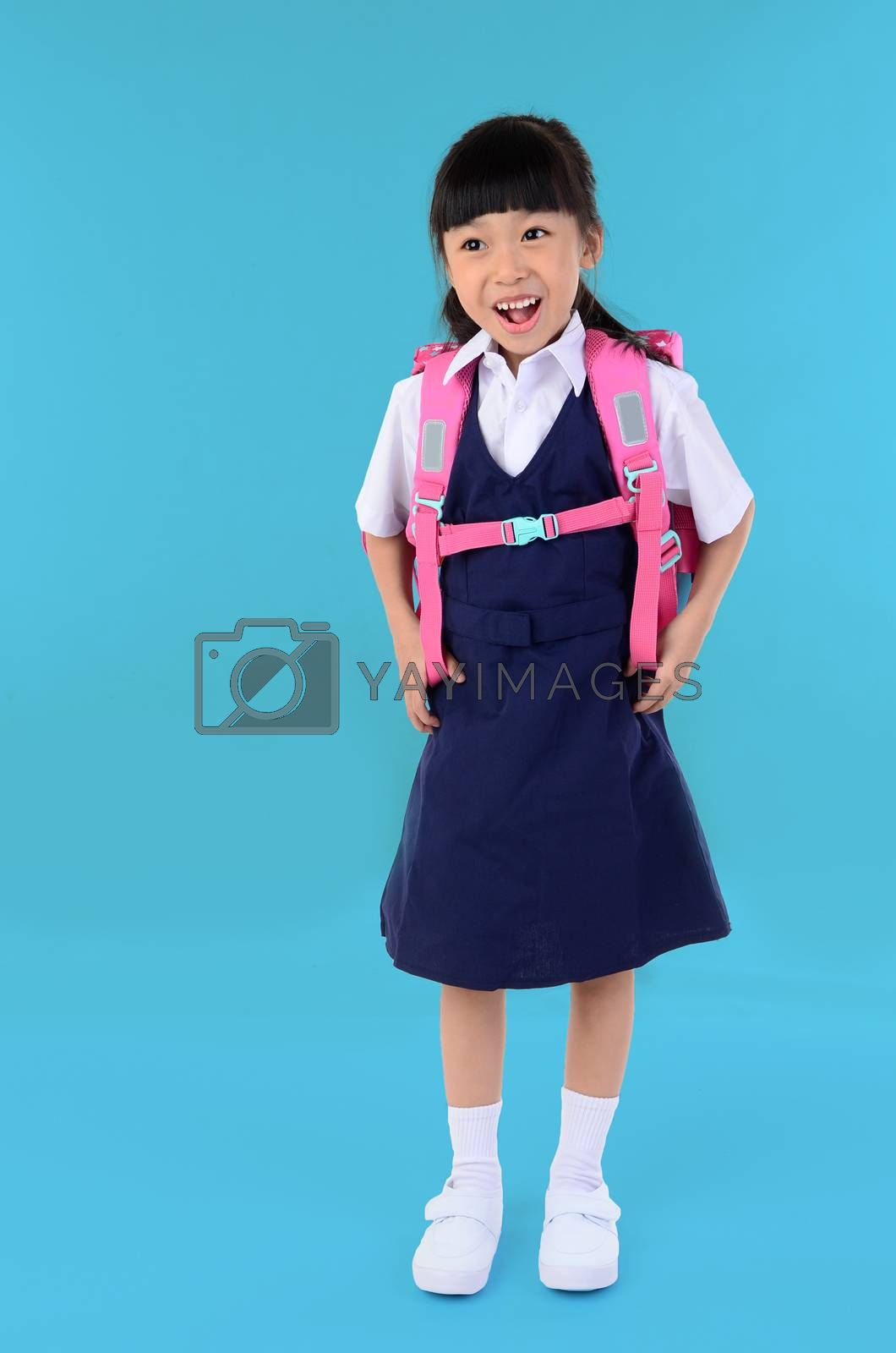 Back to school. Portrait of happy asian cute little child girl in uniform with school bag smiling when go back to school, isolated blue background.