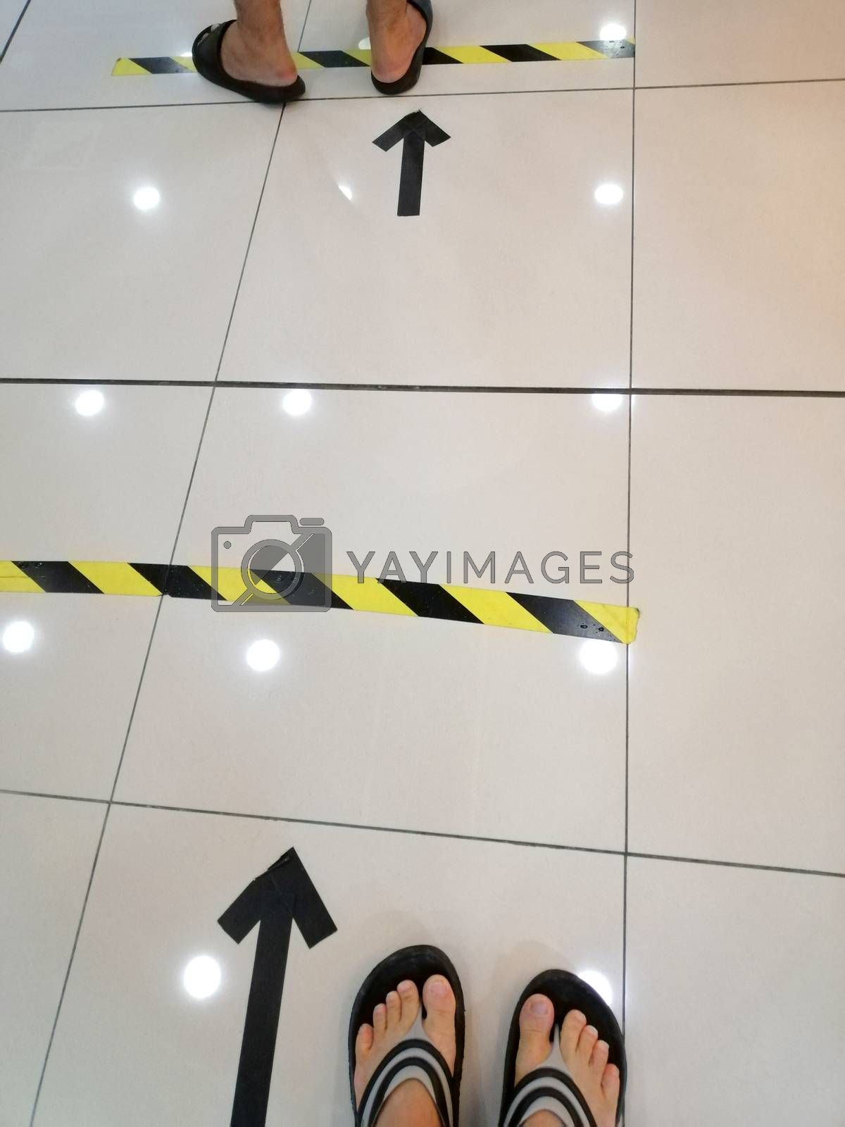 People stand in yellow black footprint  line on the floor of the store to maintain social distance. Concept of the coronavirus pandemic and prevention measures.