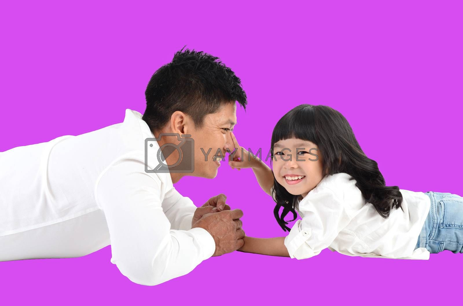 Happy father's day! joyful young dad  playing with  his cute daughter and lying on floor at home. Isolated on purple background.