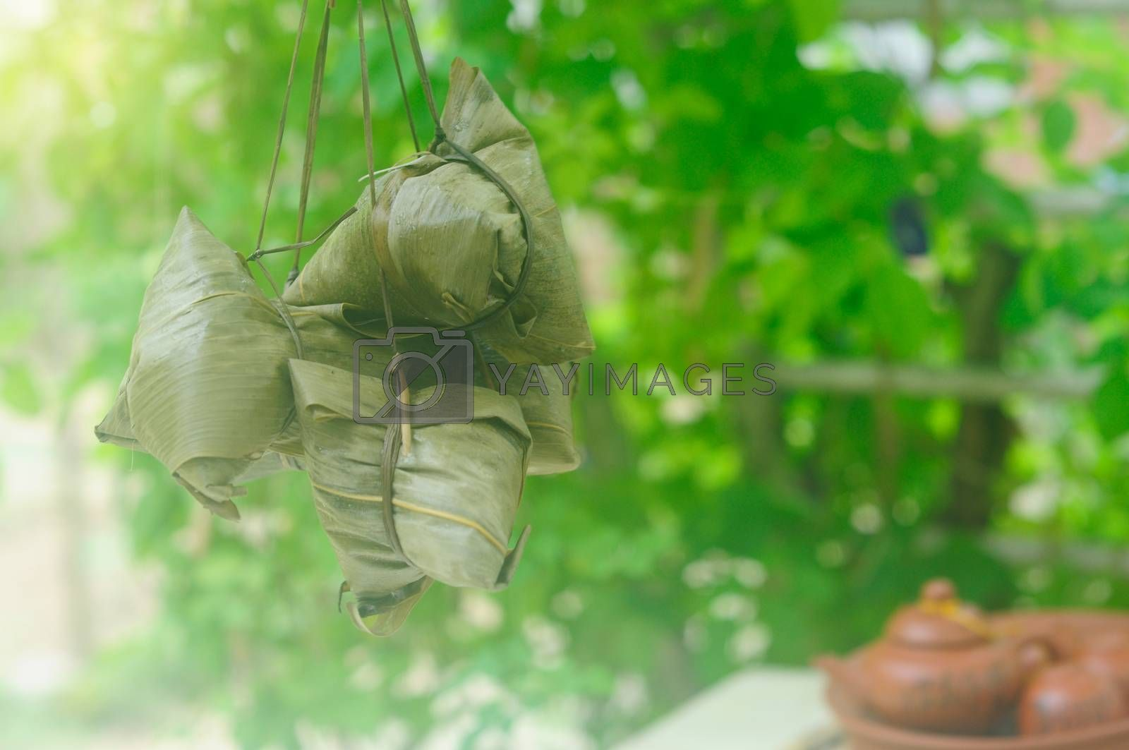 Chinese tradition food - Chinese Steamed Rice Dumpling  with bokeh background outdoor.Zongzi or traditional chinese sticky rice dumpling usually taken during festival occasion.