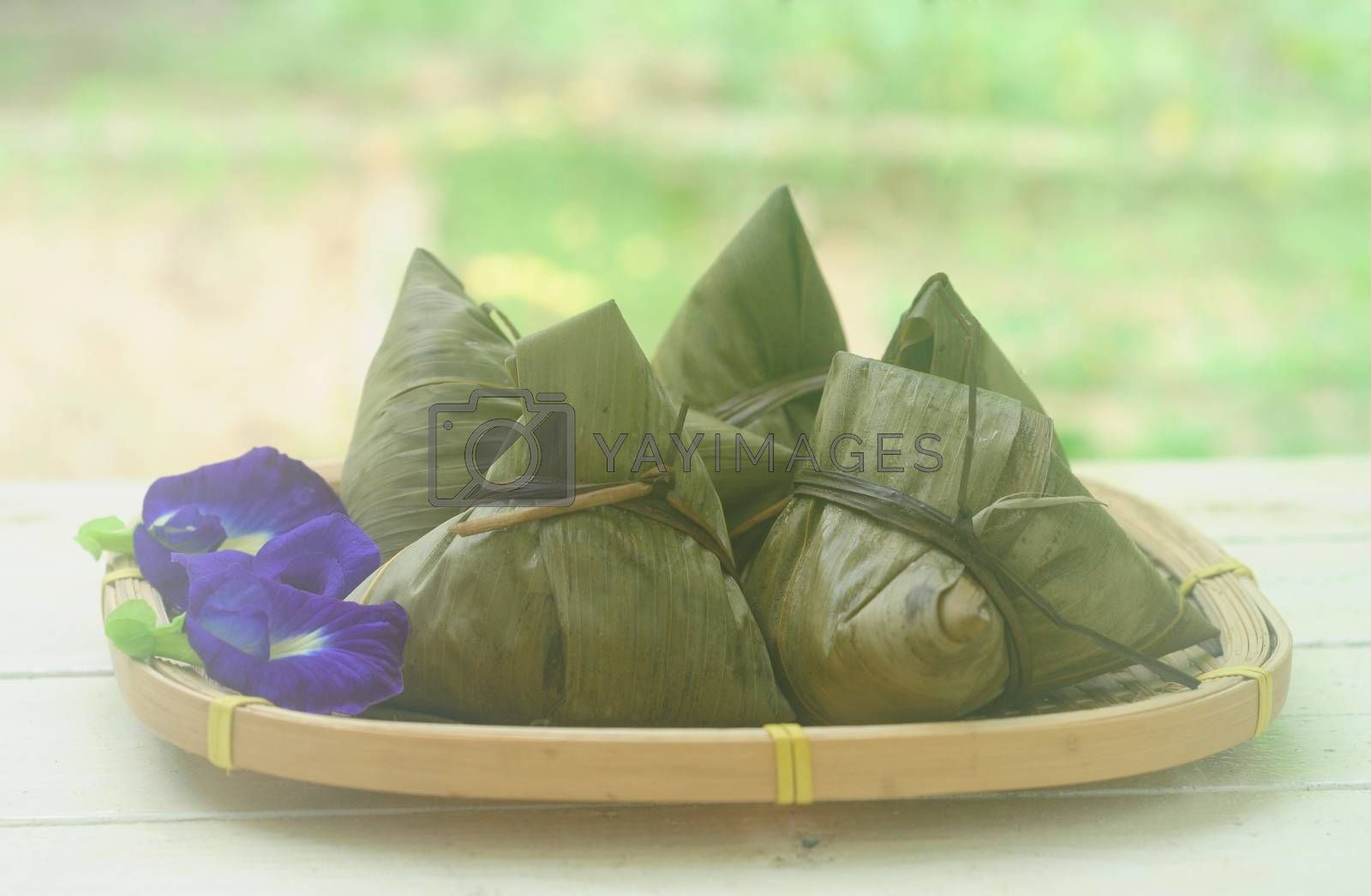 Chinese tradition food - Chinese Steamed Rice Dumpling  with blur background outdoor.Zongzi or traditional chinese sticky rice dumpling usually taken during festival occasion.