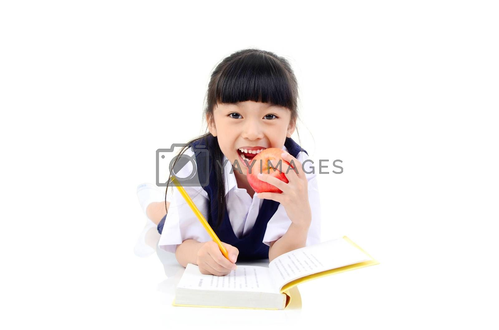 Back to school. Portrait of happy asian cute little child girl in uniform writting on the book, lying down on the floor, isolated over white  background.
