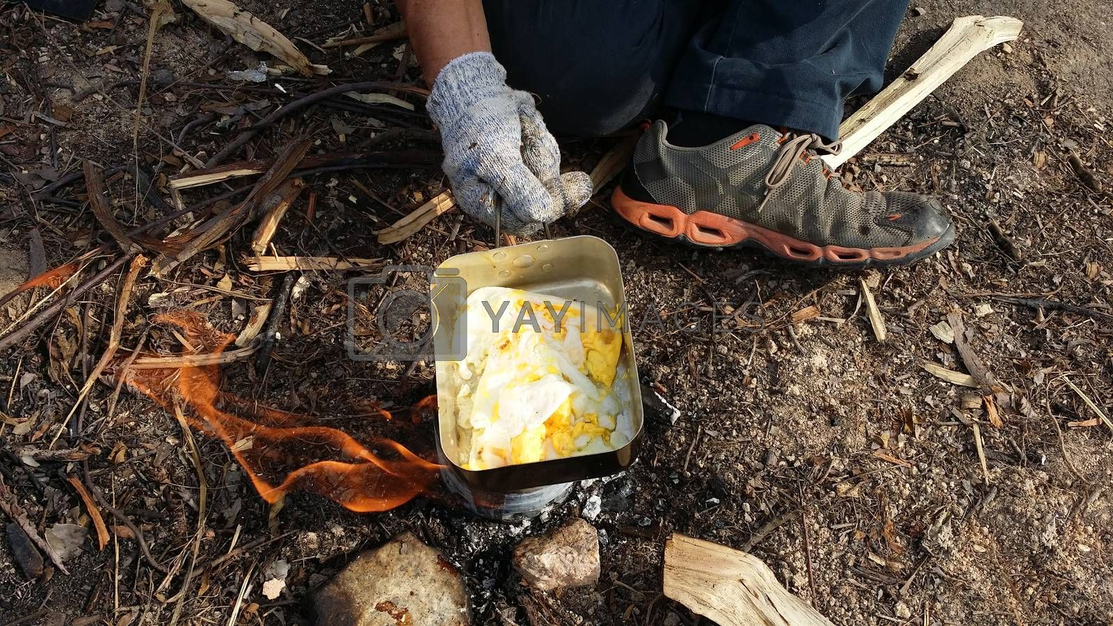 person cooking fried eggs in nature camping outdoor, cooker prepare breakfast scrambled picnic on metal pan.