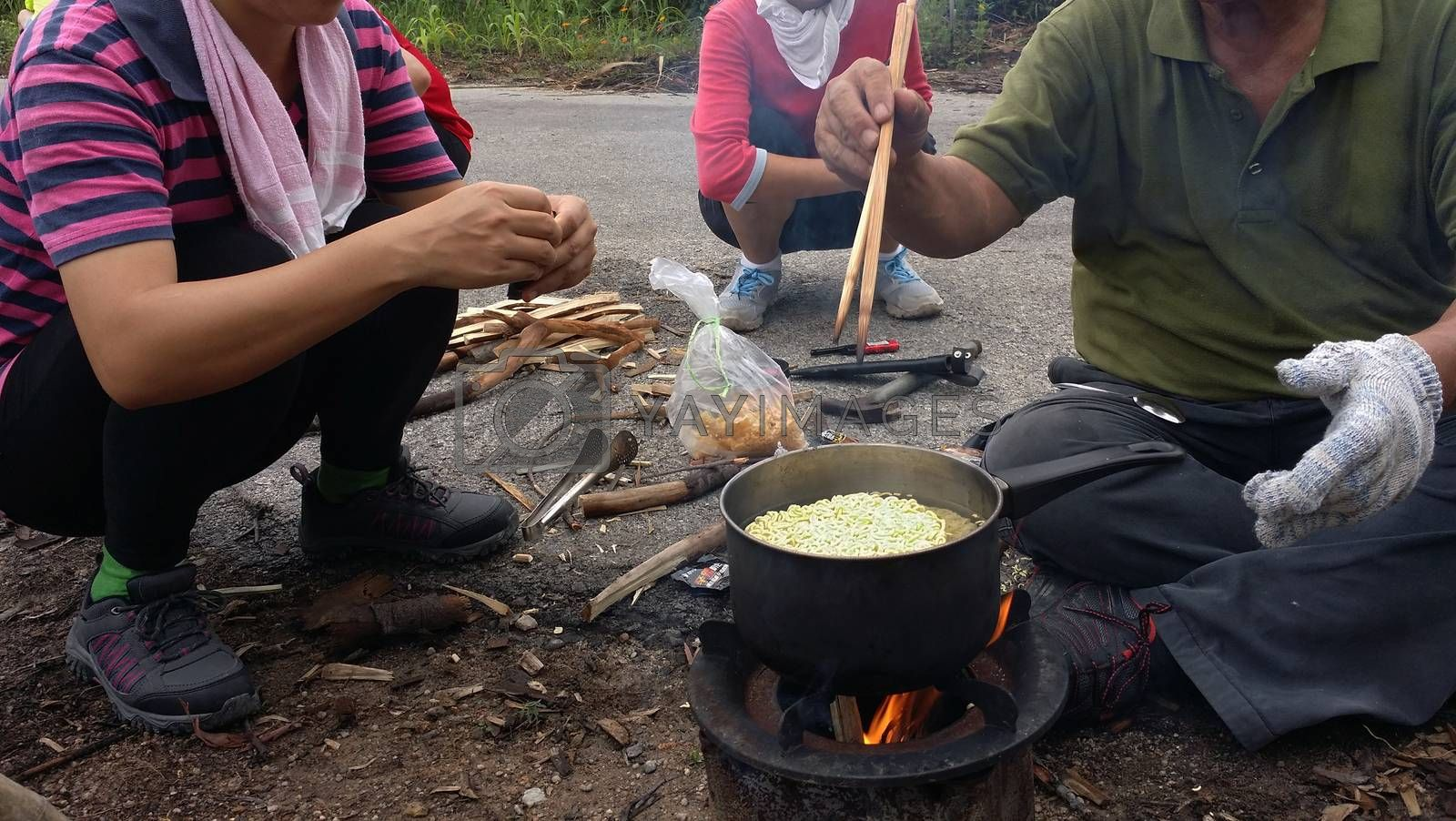 Cooking instant nodles at outdoors in black pot at picnic on fire.