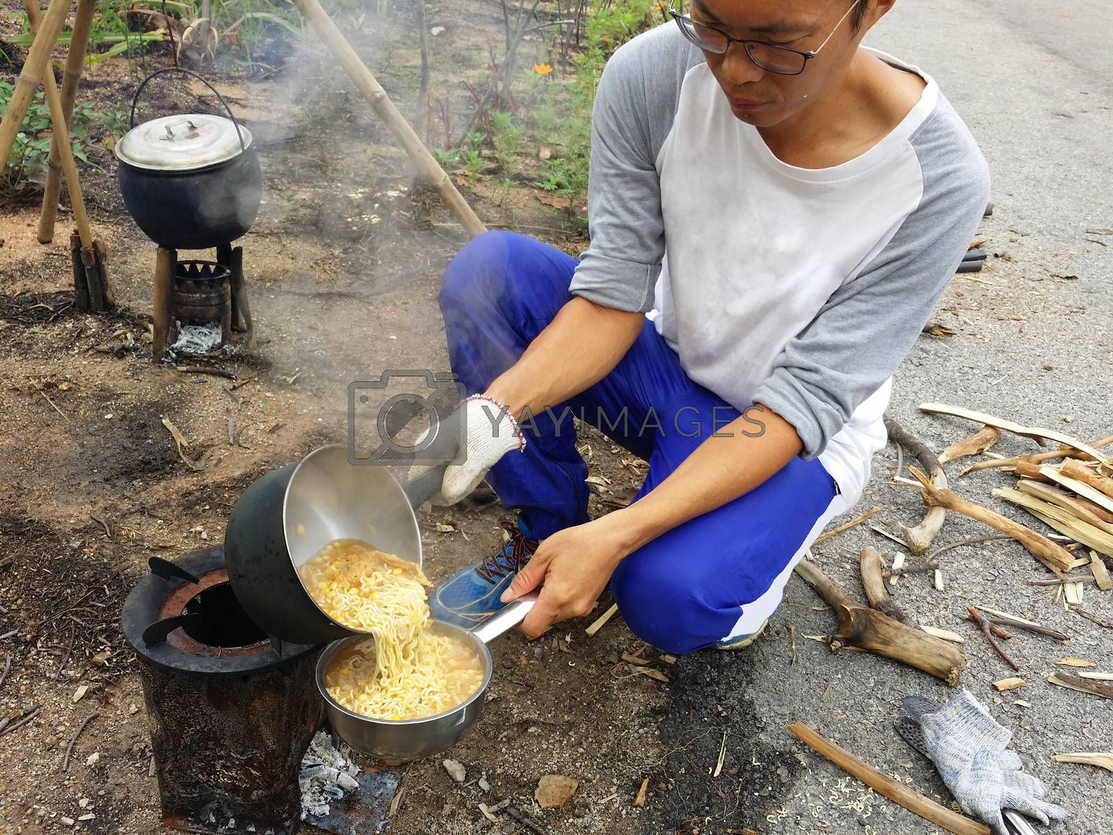 Cooking nodles at outdoors in black pot at picnic on fire