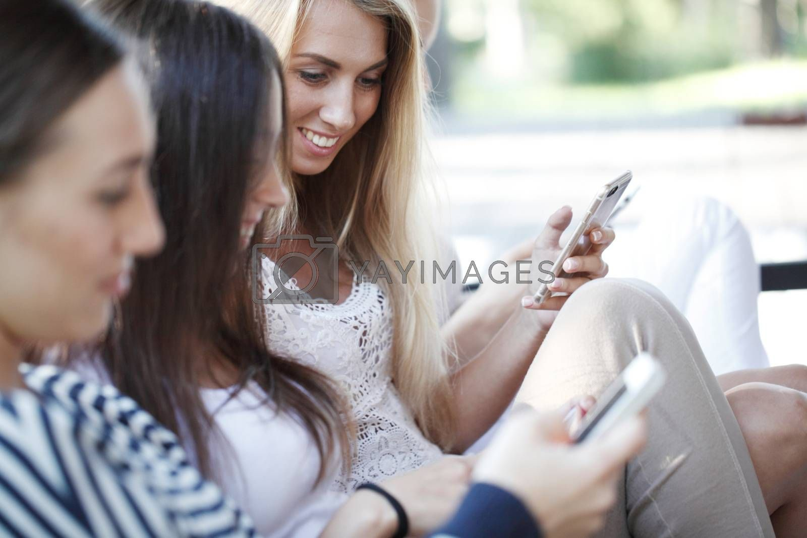 Girls chatting with their smartphones at the park