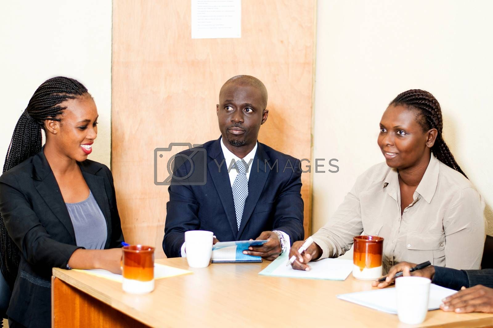 A team of smiling business people meeting  and discussing  with cups of coffee and papers to take notes in front of them