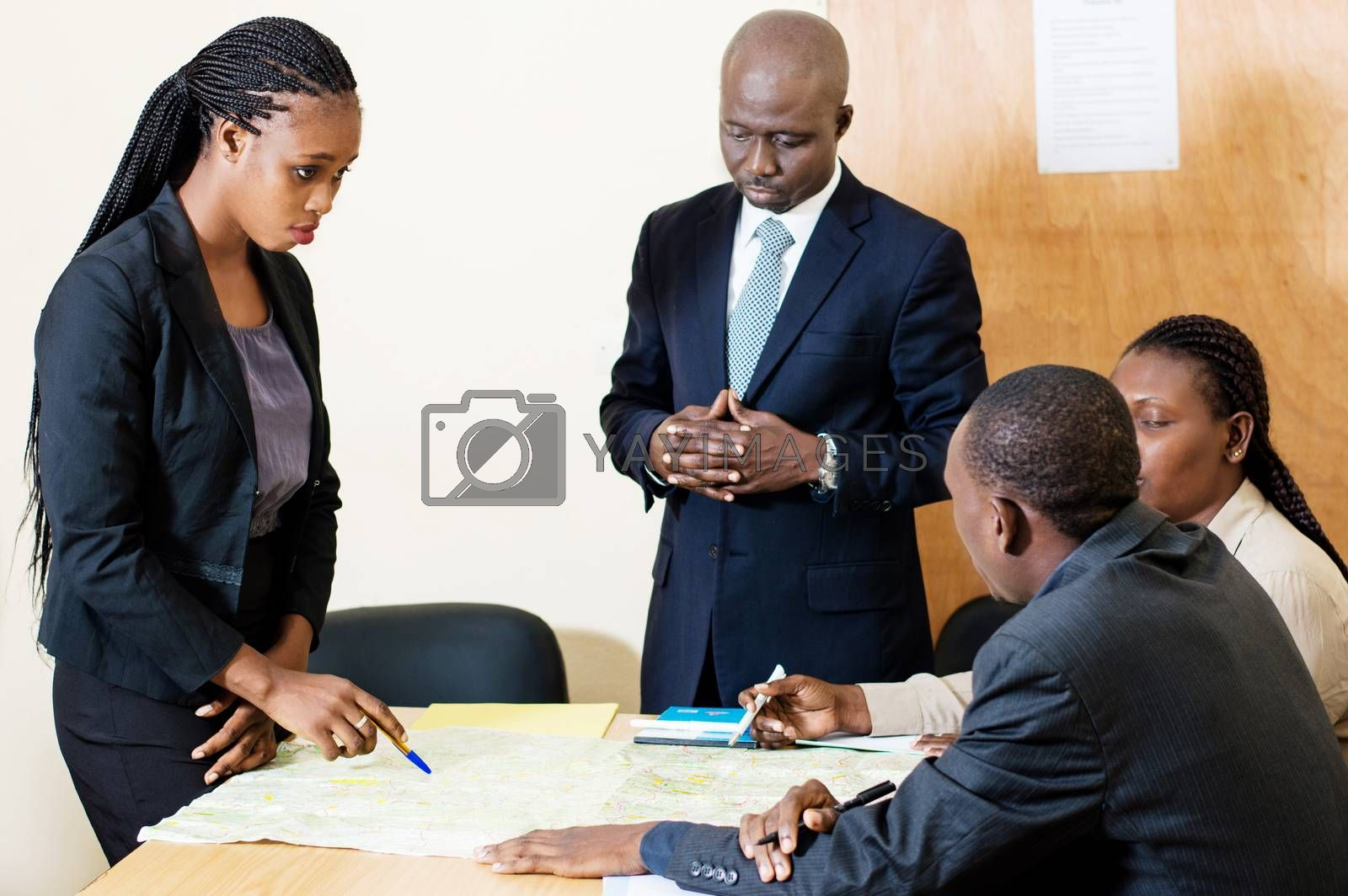 Young businesswoman shows her colleagues the different ways on the card placed in front of them.