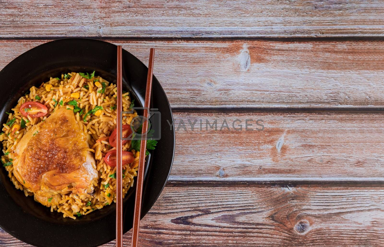 Homemade Chinese fried rice with chicken on a plate with chopsticks into the dish Asian food style