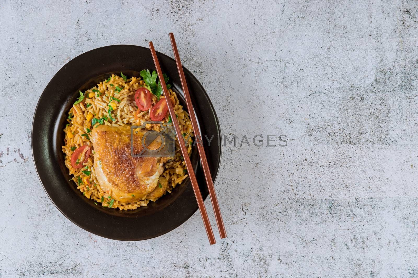Fried pasta and rice chicken with parsley and tomatoes with chopsticks