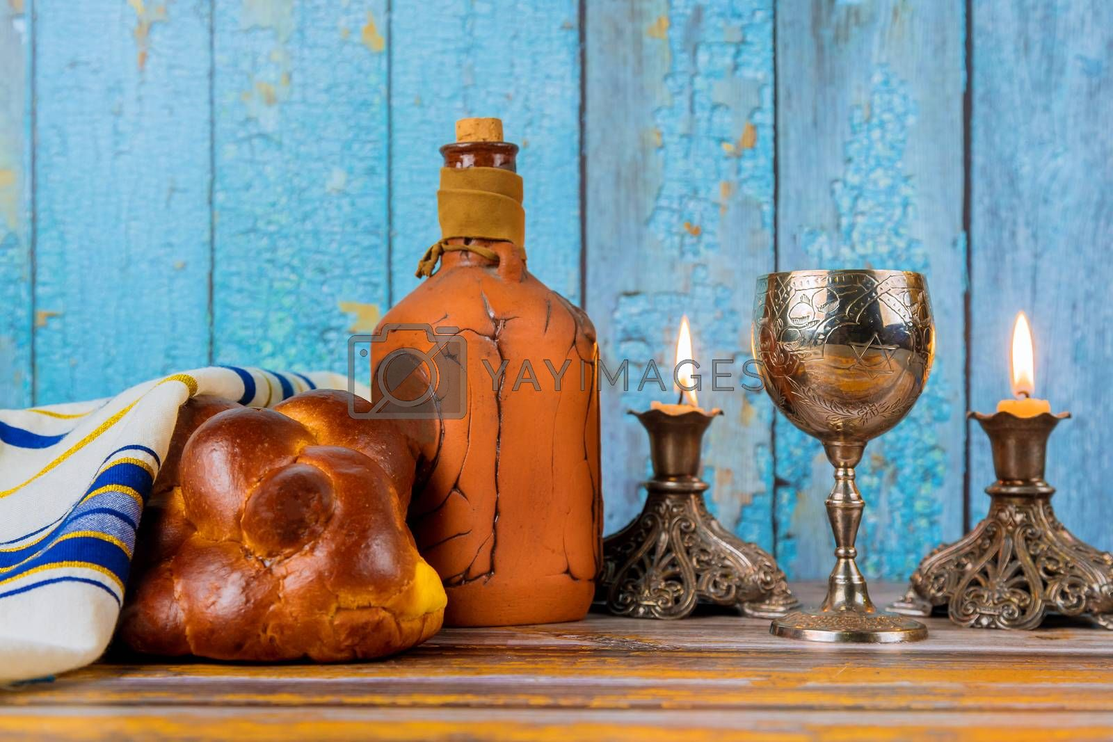 Shabbat with challah bread on a wooden table candles and cup of wine. by ungvar