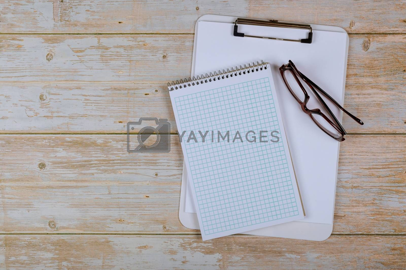 Empty notebook paper for text with glasses on old wooden background.